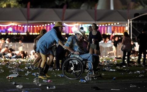 A man in a wheelchair is taken away from the Route 91 Harvest country music festival - Credit: David Becker/Getty