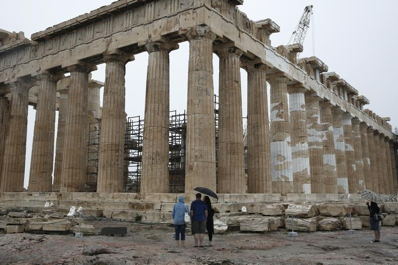 Tourists look at the temple of the Parthenon on the Acropolis hill on the eve of the World Tourism Day in Athens