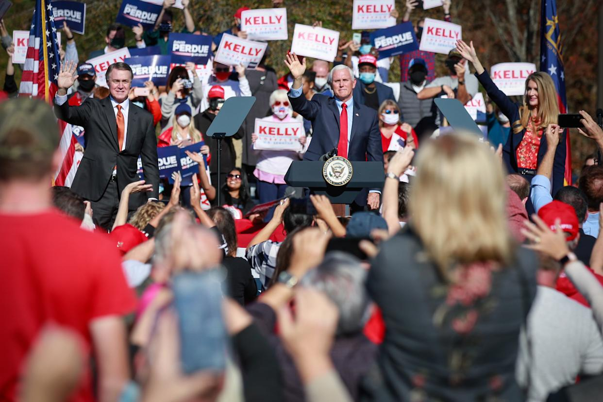 Vice President Mike Pence waves to supporters at a Defend the Majority Rally in Canton Georgia along with Sen. David Perdue (R-GA) and Sen. Kelly Loeffler (R-GA) on Friday, Nov. 20, 2020 in Canton, GA. (Jason Armond / Los Angeles Times via Getty Images)