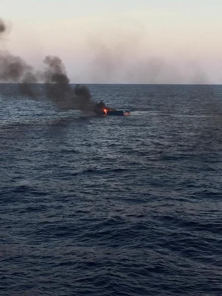 A boat burns after being set on fire by the coast guard, after they rescued migrants at the Mediterranean Sea off the coast of Libya