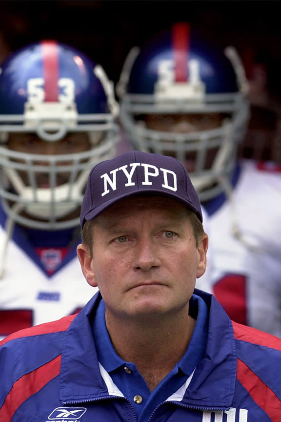 FILE - New York Giants coach Jim Fassel wears a New York Police Department cap while pausing during a moment of silence for those killed at the World Trade Center during the Sept. 11 terrorist attacks, before an NFL football game against the Kansas City Chiefs at Arrowhead Stadium in Kansas City, Mo., in this Sunday, Sept. 23, 2001, file photo. Fassel, a former coach of the New York Giants who was named NFL coach of the year in 1997 and led the team to the 2001 Super Bowl, has died. He was 71. Fassel's son, John, confirmed the death to the Los Angeles Times on Monday, June 7, 2021. According to the Los Angeles Times, Fassel was taken to a hospital in Las Vegas with chest pains and died of a heart attack. (AP Photo/Charlie Riedel, FIler)