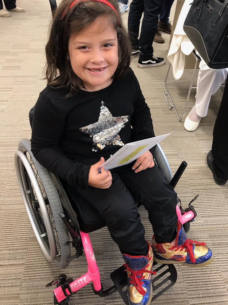 Amys daughter sitting in her pink wheelchair, smiling.
