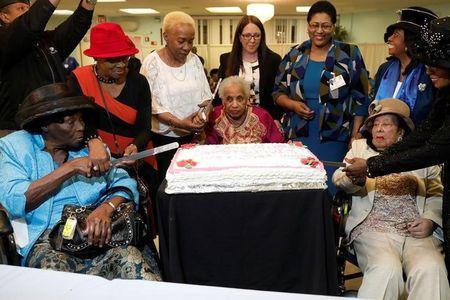 Three Over 100 Year Old Women Cut A Cake At Birthday Celebration For