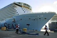 Dock workers tie the Royal Caribbean's Odyssey of the Seas to its berthing spot on June 10, 2021 in Fort Lauderdale, Florida