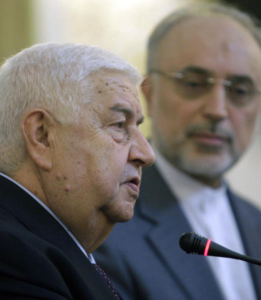 Syrian Foreign Minister Walid al-Moallem, left, speaks to journalists during a joint press conference with his Iranian counterpart Ali Akbar Salehi, in Tehran, Iran, Sunday, July 29, 2012. (AP Photo/Vahid Salemi)