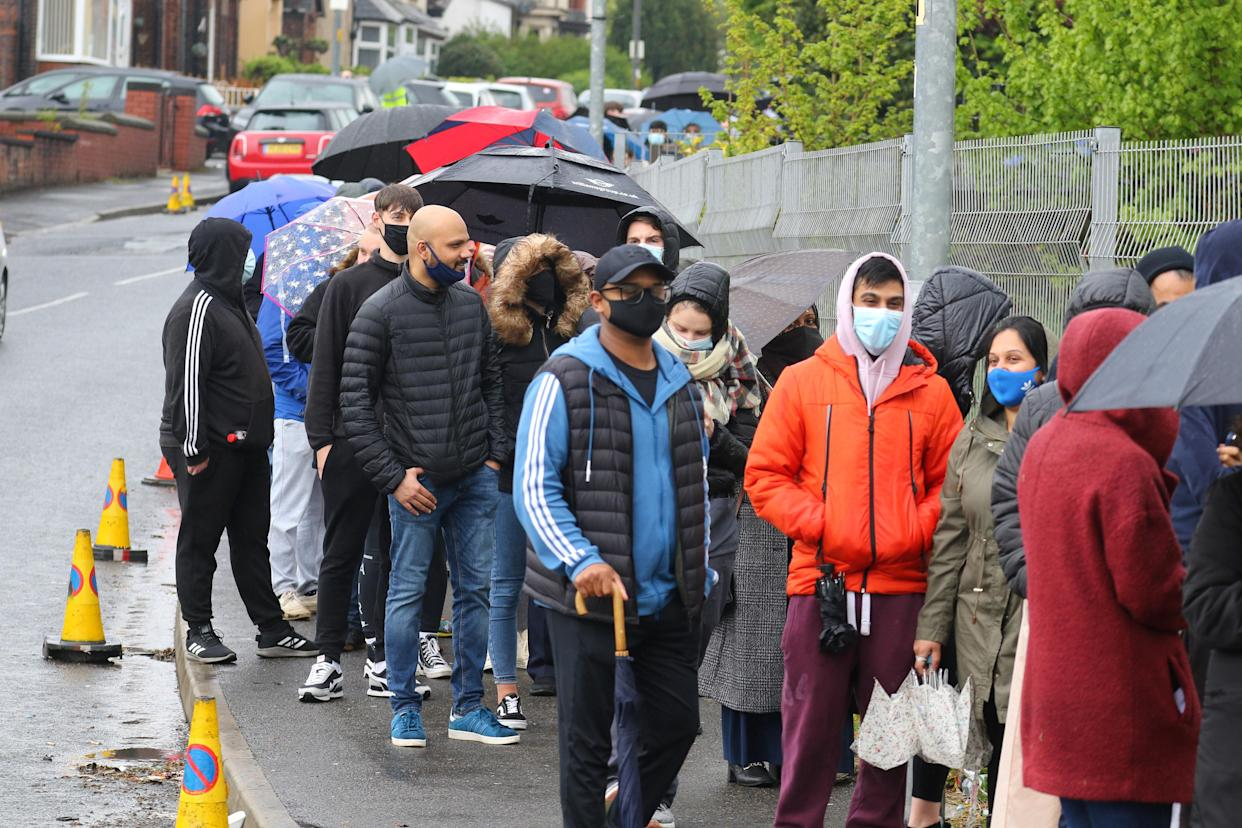 People could be seen braving the weather to queue through the streets.
