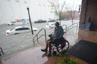 A man watches flood waters, Wednesday, Sept. 16, 2020, in downtown Pensacola, Fla. Hurricane Sally made landfall Wednesday near Gulf Shores, Alabama, as a Category 2 storm, pushing a surge of ocean water onto the coast and dumping torrential rain that forecasters said would cause dangerous flooding from the Florida Panhandle to Mississippi and well inland in the days ahead. (AP Photo/Gerald Herbert)