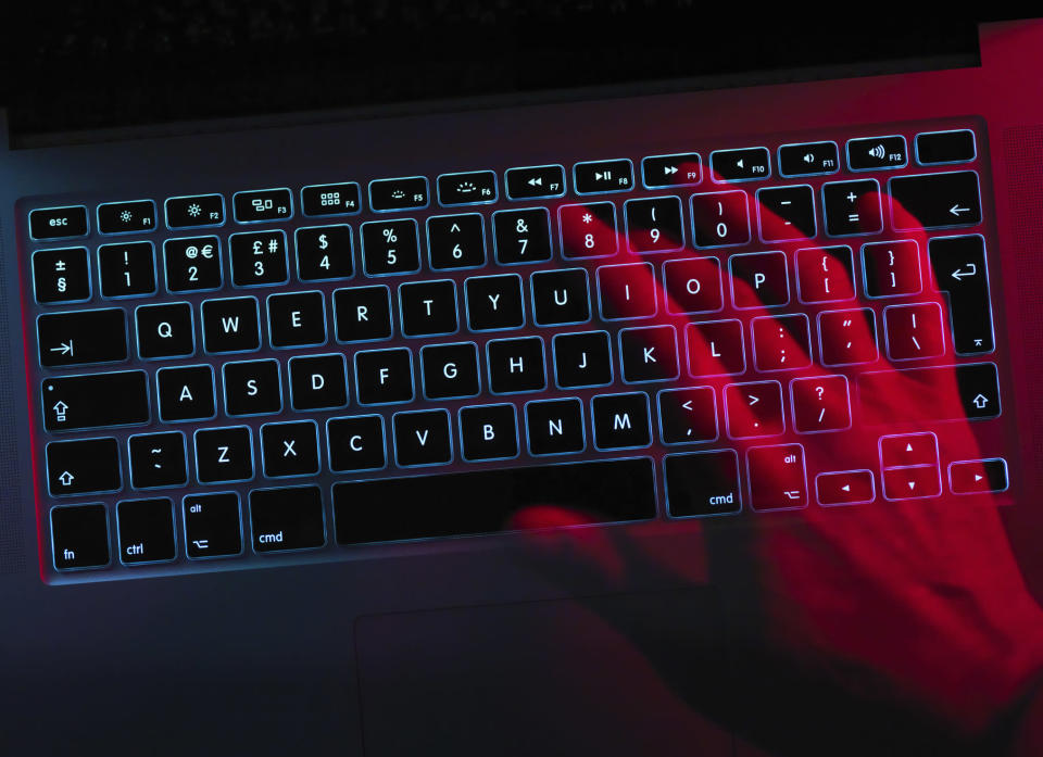 Hand working at laptop computer illustrating cyber crime