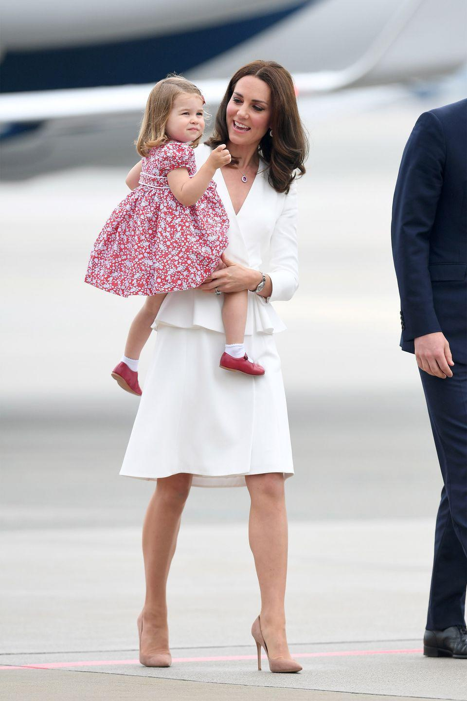 <p>In an all white Alexander McQueen coat dress with nude heels while arriving at the Warsaw airport. </p>