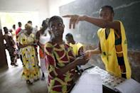 An electoral officer points at a polling booth to a voter during a presidential election at a polling station in Cotonou, Benin, March 6, 2016. REUTERS/Akintunde Akinleye