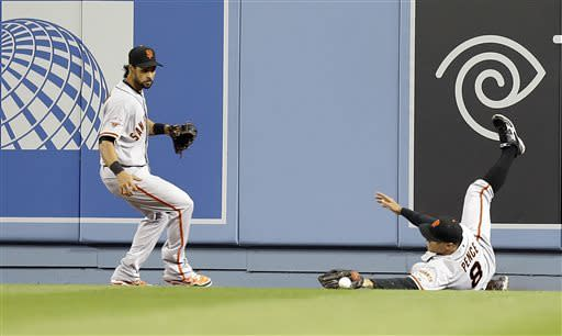 San Francisco Giants right fielder Hunter Pence and center fielder Angel Pagan just miss a fly off a long fly off the Los Angeles Dodgers A.J. Ellis that lands for a double in the second inning of a baseball game in Los Angeles Wednesday, April 3, 2013. (AP Photo/Reed Saxon)