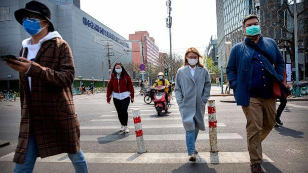 PHOTO: People wear face masks as they walk across an intersection in Beijing, China, on April 7, 2020. (Mark Schiefelbein/AP)