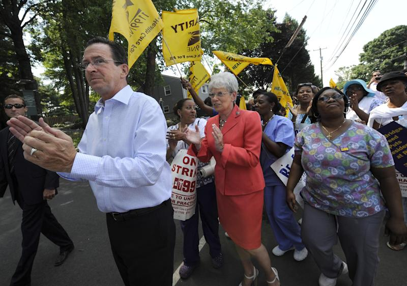 "Connecticut Gov. Dannel P. Malloy, left, and Lt. Gov. Nancy Wyman march with striking nursing home workers at Newington Health Care Center in Newington, Conn., Wednesday, July 11, 2012. Workers at five HealthBridge-owned nursing homes around the state went on strike last week after the health care company declined to return to the bargaining table. Malloy said it's clear the company has taken ""unfair actions"" against employees, citing last week's federal complaint against the company issued by the National Labor Relations Board. (AP Photo/Jessica Hill)"