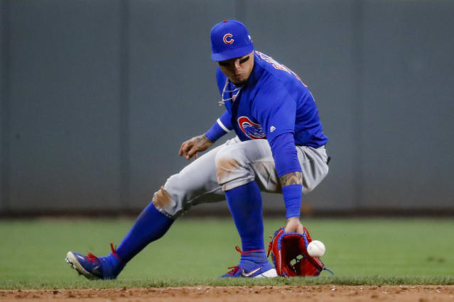 Chicago Cubs shortstop Javier Baez fields a ground ball by Cincinnati Reds' Jesse Winker in the sixth inning of a baseball game, Friday, Aug. 9, 2019, in Cincinnati. Winker was forced out at first base. (AP Photo/John Minchillo)