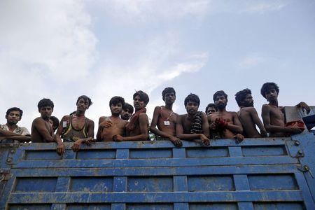 Migrants, who were found at sea on a boat, sit at the back of a truck as they are moved to Taung Pyo sub-township after landing near Kanyin Chaung jetty outside Maungdaw township, northern Rakhine state, Myanmar June 3, 2015.  REUTERS/Soe Zeya Tun