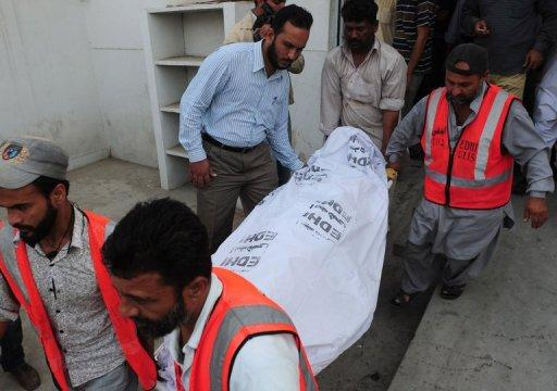"Pakistani volunteers carry the body of a policeman to a hospital following an attack by gunmen in Karachi on Thursday. Senior police official Rao Anwar said he was the target and claimed to have been threatened for a month by ""unknown terrorists"""