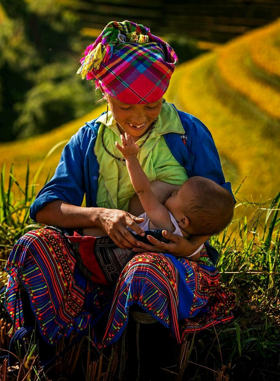 """Vietnamese photographer @Tuanngocphoto spotted this Hmong woman having a break to feed her child in Mu Cang Chai: """"Although they are working in the fields, the Hmong people still carry their children on their backs."""". [Photo: SWNS]"""