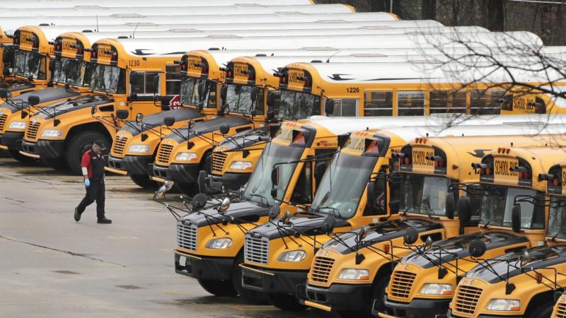 FILE - In this April 27, 2020, file photo, a worker passes public school buses parked at a depot in Manchester, N.H. School districts across America are in the midst of wrenching decisions during the summer about how to resume classes in settings radically altered by the coronavirus pandemic, with socially distanced school buses, virtual learning, outdoor classrooms and quarantine protocols for infected children as the new norm. (AP Photo/Charles Krupa, File)