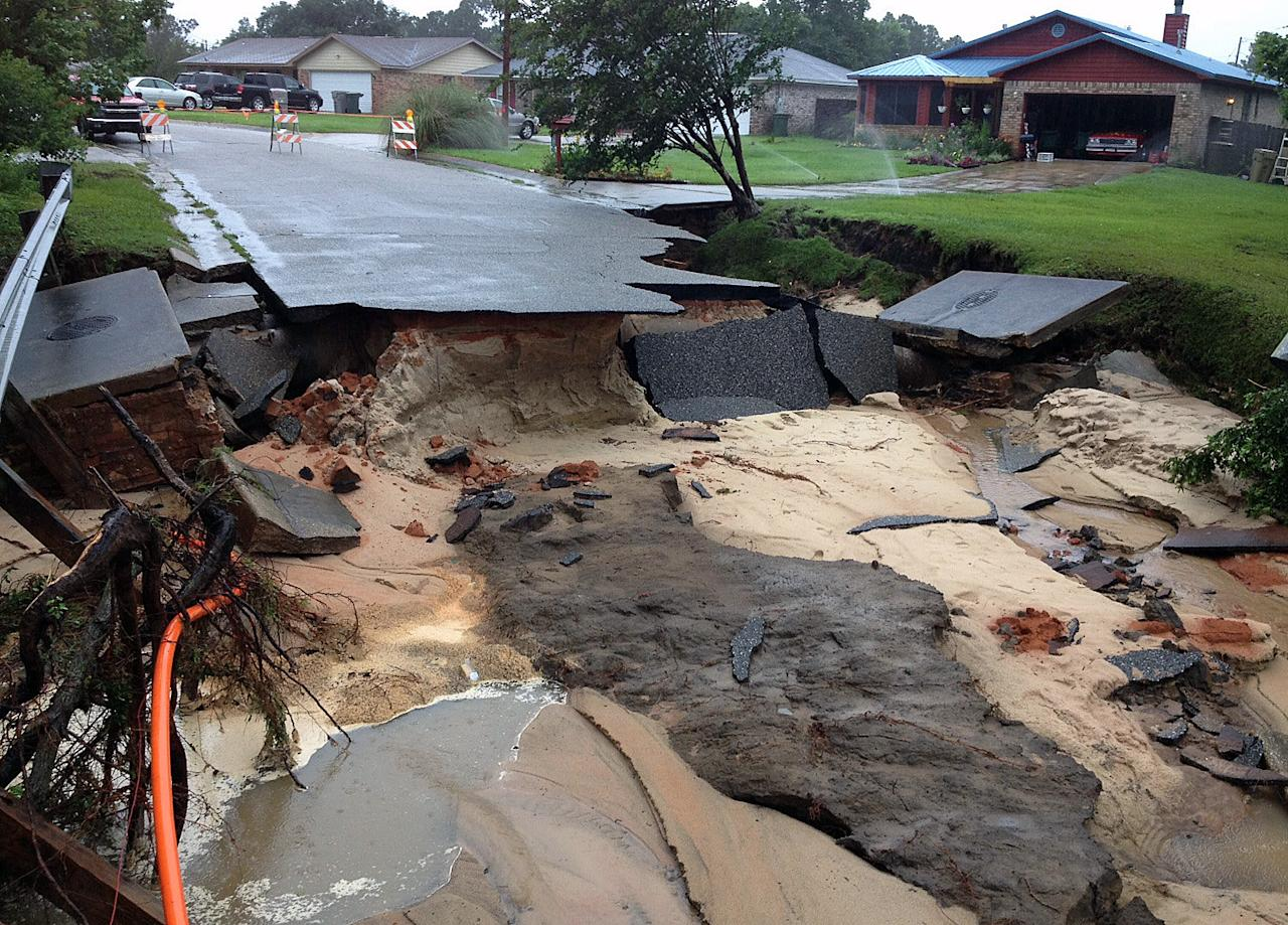 A section of Oak Valley Drive in Escambia County, Fla., is washed out on Sunday, June 10, 2012, after heavy rains fell on Saturday, in Pensacola, Fla. Floodwaters from torrential rains damaged homes and closed roads throughout the Florida Panhandle, cutting power to the county jail and sending residents to emergency shelters as the area braced for additional rains Sunday. (AP Photo/The Pensacola News Journal, Tony Giberson) NO SALES; MANDATORY CREDIT: TONY GIBERSON/PENSACOLA NEWS JOURNAL AND PNJ.COM