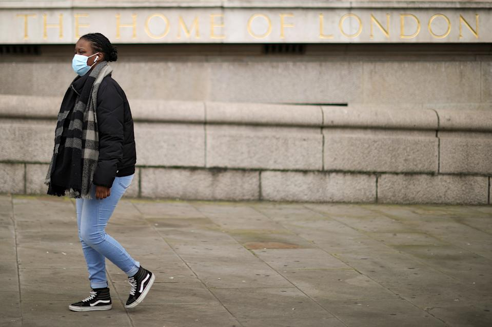 A woman wearing a face mask walks on a street, amid the coronavirus disease (COVID-19) outbreak, in London, Britain February 22, 2021. REUTERS/Hannah McKay