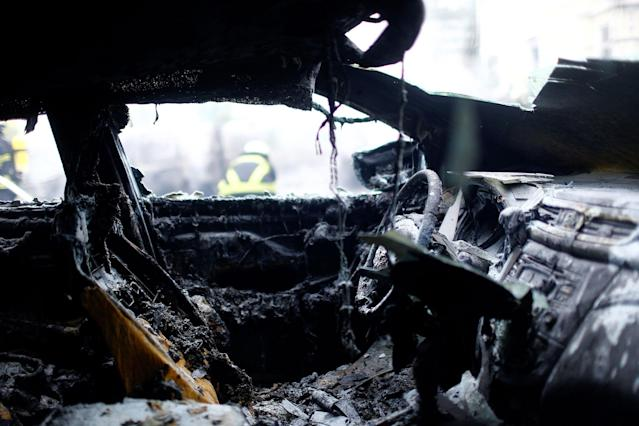 <p>The interior of a burnt down car is seen as firefighters work in the background during the G20 summit in Hamburg, Germany, July 7, 2017. (Photo: Hannibal Hanschke/Reuters) </p>