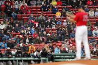 Fans watch as Boston Red Sox's Nathan Eovaldi, foreground, pitches during the first inning of a baseball game against the Miami Marlins, Saturday, May 29, 2021, in Boston. Saturday marks the end of most COVID-19 restrictions in Massachusetts. (AP Photo/Michael Dwyer)