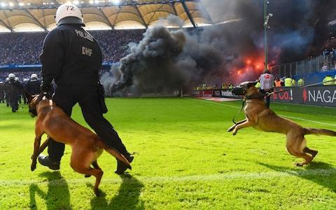 Ten-man Hamburg were relegated from the Bundesliga for the first time on Saturday, sparking angry fan demonstrations, despite the team pulling off a 2-1 home victory over Borussia Monchengladbach. HSV had played in the German top flight since their foundation and in the Bundesliga since it began in 1963 but, after several flirtations with the drop in recent years, they have finally bowed out. Aaron Hunt converted an early penalty to put them on the right track and former Tottenham midfielder Lewis Holtby re-established their lead after Josip Drmic had levelled for Monchengladbach. The home side were reduced to 10 men as Bobby Wood received a second yellow card for a foul after 71 minutes, but - despite Hamburg's efforts to hold on for maximum points - Wolfsburg's 4-1 triumph over bottom side Cologne meant they could not be caught. Instead the Wolves will tackle a relegation/promotion play-off against second-division side Holstein Kiel. Police dogs were brought onto the pitch as fans caused trouble in the stands Credit: AFP It took Josuha Guilavogui only 41 seconds to boost the Wolves ahead, yet Cologne equalised with a classy chip from Jonas Hector. Divock Origi restored Wolfsburg's lead from close range after the break and Robin Knoche ensured they would finish 16th with his 71st-minute effort. Josip Brekalo added gloss to the scoreline at the death. When news that the full-time whistle had blown in Wolfsburg filtered through, Hamburg fans invaded the pitch at the Volksparkstadion, igniting flares and forcing a lengthy suspension as order was restored. Freiburg went into the final day vulnerable to being sucked into the play-off spot by Wolfsburg, but their 2-0 win over Augsburg negated that risk, Nicolas Hofler and Tim Kleindienst grabbing the goals. Hamburg have been relegated from the Bundesliga for the first time in their history Credit: Bongrats Stuttgart spoiled Bayern Munich's title party and Jupp Heynckes' last game in charge of the champions by producing a surprise 4-1 success at the Allianz Arena. Daniel Ginczek scored the first goal of his brace after just five minutes, only for Corentin Tolisso to peg Stuttgart back from a stunning Robert Lewandowski assist. Tassos Donis rocked Bayern again with a goal on the counter-attack before Chadrac Akolo and Ginczek struck to confirm the shock result. It is the first time in over nine years Bayern had conceded four goals at home in the league, although they will not have cared too much as they lifted the Meisterschale trophy. A display burns inside the stadium Credit: AFP Hoffenheim and Borussia Dortmund won the race for the remaining Champions League spots, even though the former club subjected the latter to a 3-1 defeat at the Rhein-Neckar-Arena. Andrej Kramaric fired TSG ahead, with Marco Reus levelling before Adam Szalai and Pavel Kaderabek steered Hoffenheim into third place, while Dortmund took fourth. Missing out were Bayer Leverkusen, who will be frustrated to have to settle for the Europa League after a 3-2 home win over Hannover. Lucas Alario produced two classy strikes, and Julian Brandt one, before Hannover hit back through Niclas Fullkrug and Martin Harnik, meaning Bayer missed out on the Champions League due to their inferior goal difference to BVB. Everton loanee Ademola Lookman ran the show with a goal and two assists as RB Leipzig booked Europa League football by winning 6-2 at Hertha Berlin. Dayot Upamecano gave the capital club the lead with a header but Leipzig promptly levelled through Vedad Ibisevic and were 3-1 up by half-time as Lookman struck before setting up Jean-Kevin Augustin. Timo Werner pushed the visitors further clear with a goal on the break and Lookman found Augustin for a match-killing strike shortly before the hour mark. Salomon Kalou would later notch Hertha's second before Bruma made it six for Leipzig late on. Elsewhere, Guido Burgstaller's bullet header saw Schalke edge Eintracht Frankfurt 1-0 and Werder Bremen left it late to triumph 2-1 at Mainz, Theodor Gebre Selassie grabbing the winner after Florian Kainz had cancelled out Jean-Philippe Gbamin's opener.