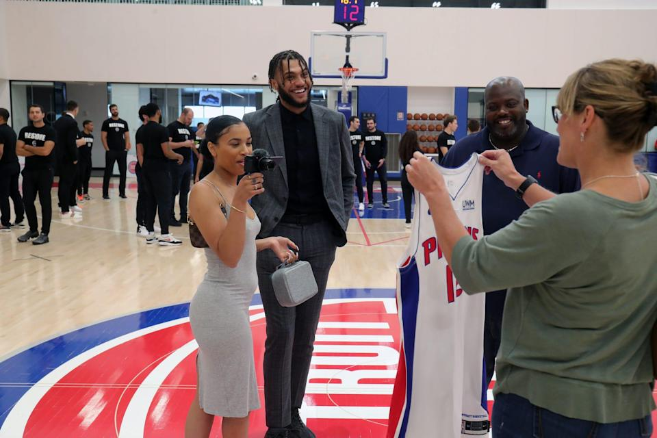 Pistons second-round pick Isaiah Livers, his girlfriend, Hope Hale, and dad, Morris, watch Livers' mom, Angela, pose with Livers' jersey after the news conference on Friday, July 30, 2021, at the team's practice facility in Detroit.