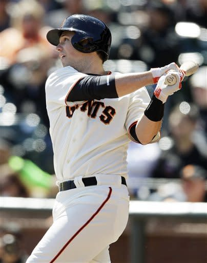San Francisco Giants' Buster Posey hits an RBI single off Oakland Athletics starting pitcher Tommy Milone during the first inning of their exhibition baseball game in San Francisco, Wednesday, April 4, 2012. (AP Photo/Eric Risberg)