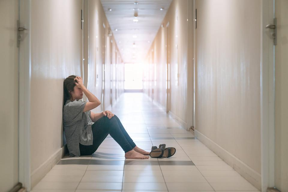 woman suffering from depression sat in the corridor and cried.