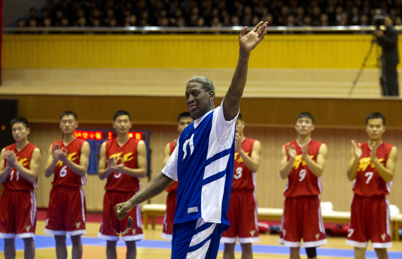 "Dennis Rodman waves at North Korean leader Kim Jong Un, seated above in the stands, after singing ""Happy Birthday"" to him before an exhibition basketball game at an indoor stadium in Pyongyang, North Korea in January 2014."