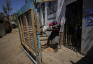 Haitian Edanold Delva, who has permanent residency in Chile, plays with his Chilean-born son Moises, 2, outside their home they share with Delva wife, Moises' mother, Jacqueline Michel, who also has residency, in the Bosque Hermoso camp settled by migrants in Lampa, Chile, Friday, Oct. 1, 2021. Most Haitians are fleeing earthquakes, hurricanes, political turbulence and poverty in their homeland. (AP Photo/Esteban Felix)