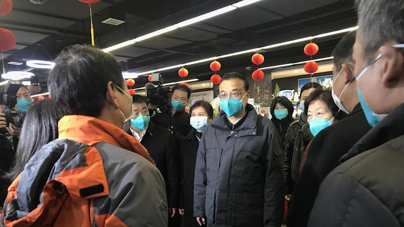 China's Premier Li Keqiang (C) is the most senior leader to visit Wuhan since the virus outbreak
