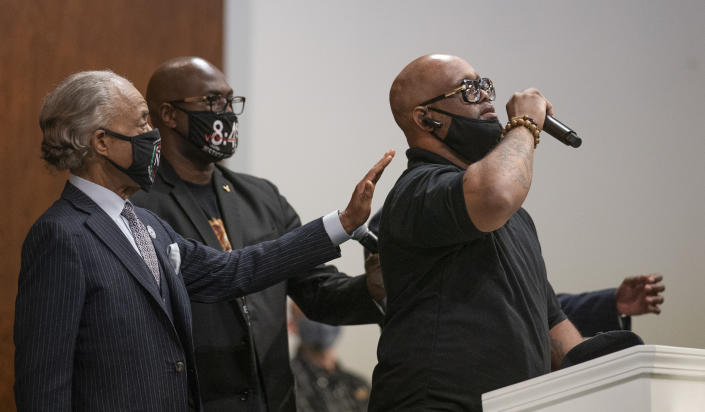 Terrence Floyd, right, brother of George Floyd, speaks during a prayer service at Greater Friendship Missionary Church as The Rev. Al Sharpton, left, and his brother Philonise Floyd place their hands on his back, Sunday, March 28, 2021, in Minneapolis. Opening statements are set for Monday in the trial of a former Minneapolis police officer charged with murder and manslaughter in George Floyd's death. (Jerry Holt/Star Tribune via AP)