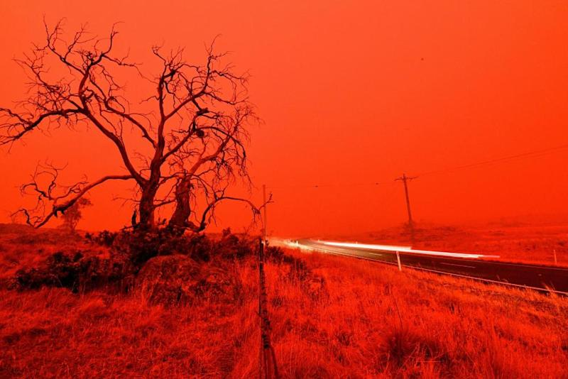 A long exposure picture shows a car commuting on a road as the sky turns red from smoke of the Snowy Valley bushfire on the outskirts of Cooma.