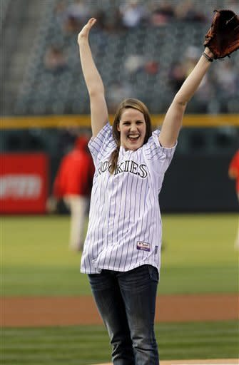 Four-time Olympic gold medalist Missy Franklin reacts after throwing out the ceremonial first pitch before the Colorado Rockies host the Arizona Diamondbacks in the first inning of a baseball game in Denver on Saturday, Sept. 22, 2012. (AP Photo/David Zalubowski)