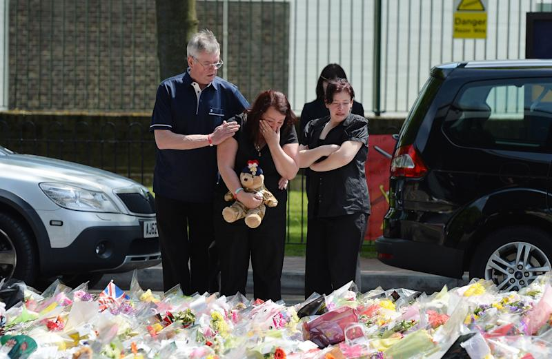 Lyn Rigby, mother of Drummer Lee Rigby, holding a teddy bear joins other family members as they look at floral tributes outside Woolwich Barracks left by well wishers as they visited the scene of the 25-year-old soldier's murder in Woolwich, south-east London, Sunday May 26, 2013. (AP Photo/John Stillwell, PA). UNITED KINGDOM OUT - NO SALES - NO ARCHIVES