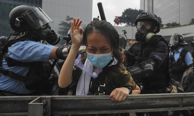 A protester reacts as she is tackled by riot police during a massive demonstration outside the legislative council in Hong Kong