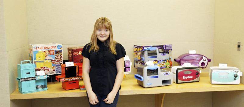 FILE - In this file photo provided by Hasbro, McKenna Pope poses in front of earlier models of the Easy-Bake Oven during her trip to the Hasbro headquarters in Pawtucket, R.I. Hasbro has announced it has been developing an Easy-Bake Oven in the gender-neutral colors of black and silver. It made the announcement after meeting with Pope, whose online petition asking the company to make one attractive to all kids gathered tens of thousands of signatures. Hasbro says it knows both boys and girls have fun playing with the Easy-Bake. (AP Photo/Hasbro, File)