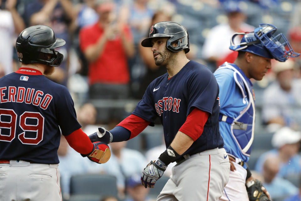 Boston Red Sox' J.D. Martinez, center, is congratulated by Alex Verdugo, left, after hitting a two-run home run as Kansas City Royals catcher Salvador Perez, right, looks away in the fifth inning of a baseball game at Kauffman Stadium in Kansas City, Mo., Saturday, June 19, 2021. (AP Photo/Colin E. Braley)