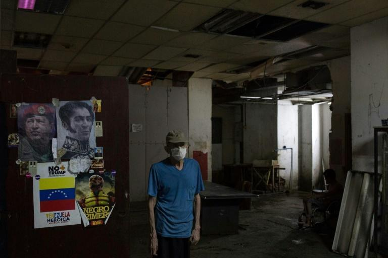 A man stands next to posters depicting Venezuelan liberator Simon Bolivar (R) and late Venezuelan leader Hugo Chavez, at the halls of a shelter located in the basement of the Sudameris public building in Caracas
