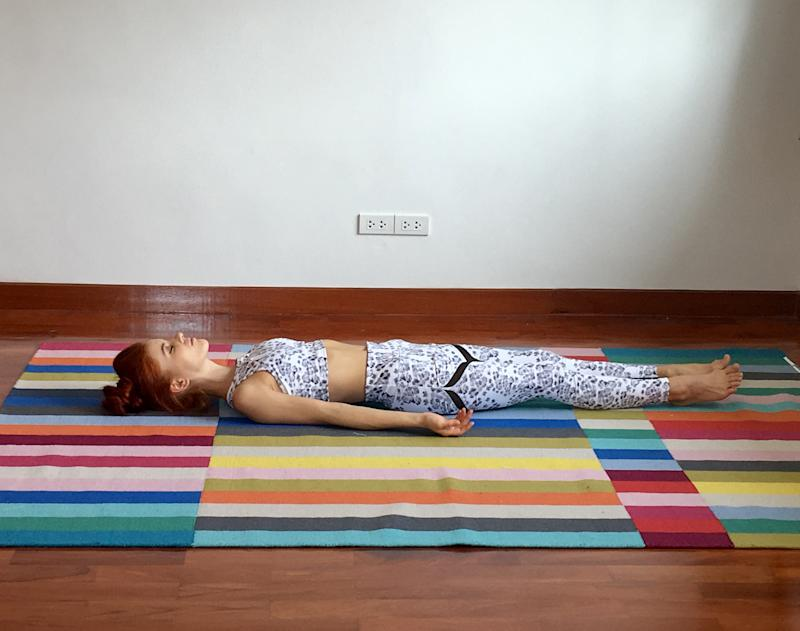 Woman Lying On Bed Against Wall At Home