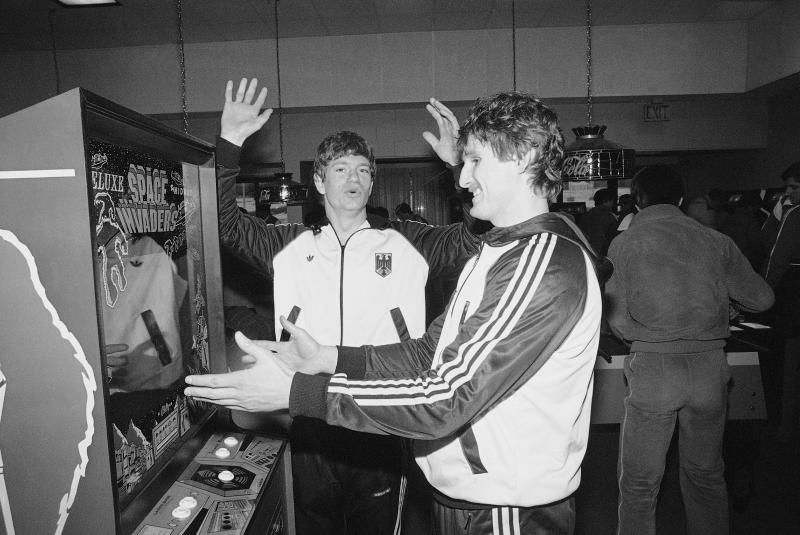 West German ice hockey players Franz Reindl, left, and Ernst Hoefner enjoy a game at the space invaders electronic games machine, as they relax in the games room of the Olympic village, Monday, Feb. 11, 1980 in Lake Placid, New York. (AP Photo)