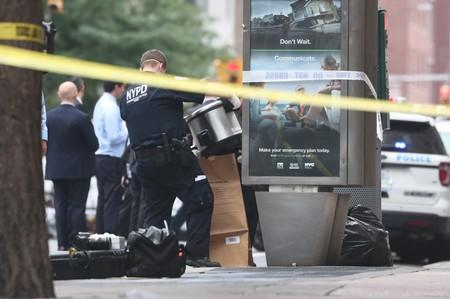 A NYPD officer is seen collecting evidences near West 16th Street and Seventh Avenue as police were investigating suspicious packages in Manhattan