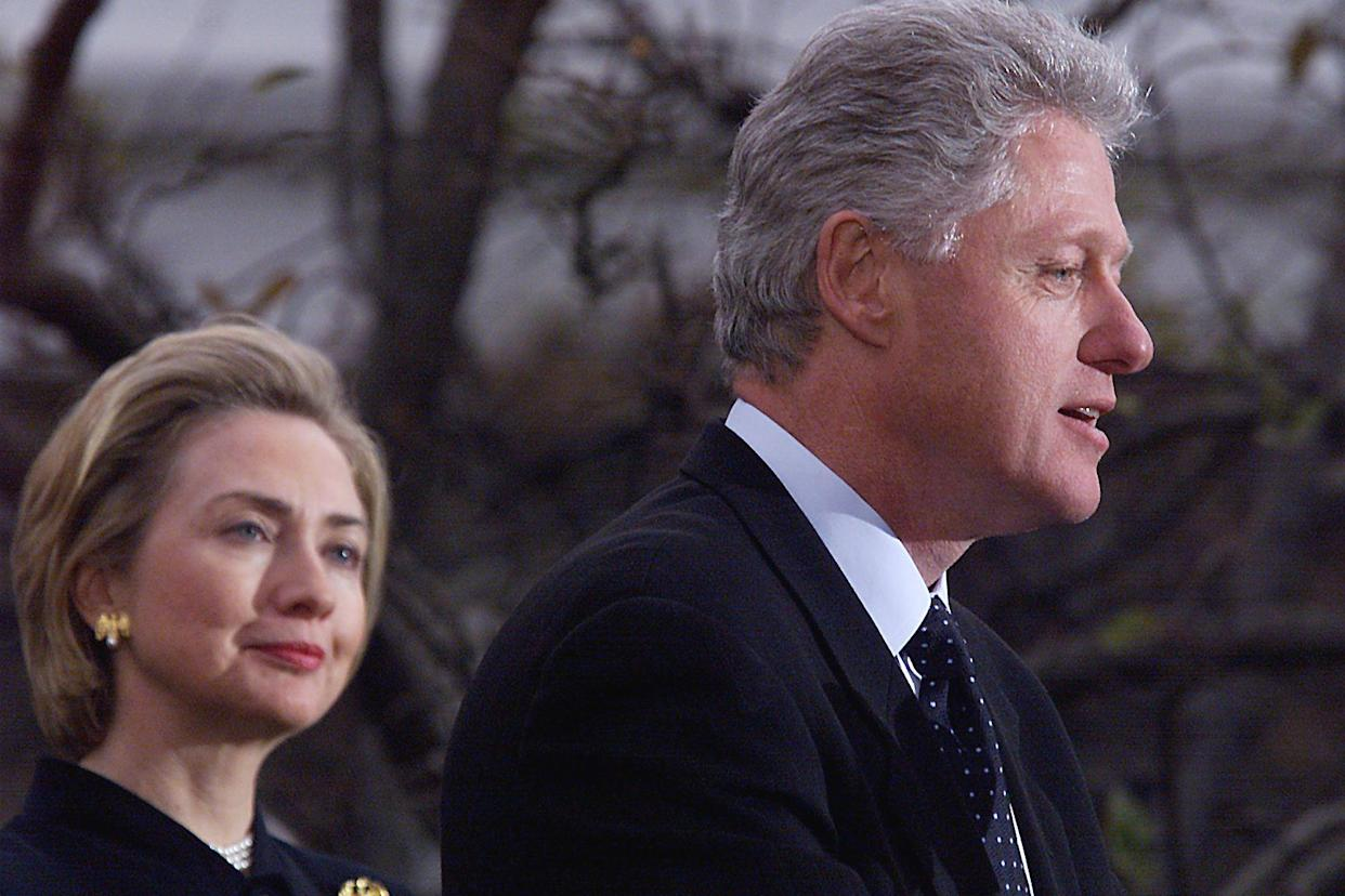 President Bill Clinton, with first lady Hillary Clinton, makes a statement to reporters following his impeachment by the House. (Photo: Tim Sloan/AFP via Getty Images)