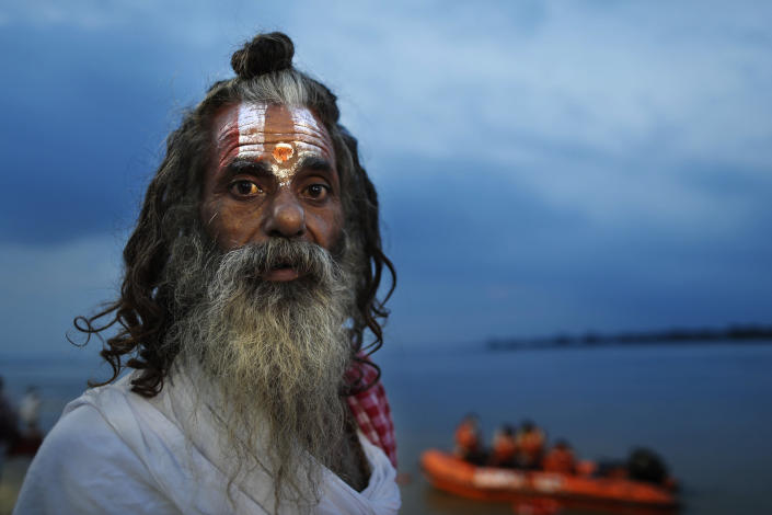 A Hindu holy man looks at a decoration on the ghats of the river Saryu as part of preparations for the groundbreaking ceremony of a temple to the Hindu god Ram in Ayodhya, in the Indian state of Uttar Pradesh, Monday, Aug. 3, 2020. As Hindus prepare to celebrate the groundbreaking of a long-awaited temple at a disputed ground in northern India, Muslims say they have no firm plans yet to build a new mosque at an alternative site they were granted to replace the one torn down by Hindu hard-liners decades ago. (AP Photo/Rajesh Kumar Singh)