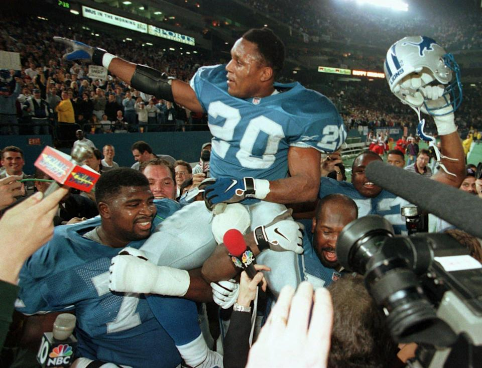 Barry Sanders is carried off the field in 1997 after becoming just the third running back ever to rush for 2,000 yards in a season. (AP)