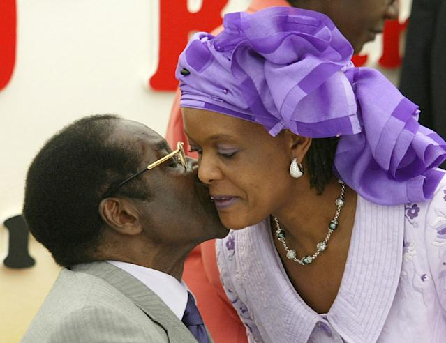 <p>Mugabe kisses his wife, Grace, at his 80th birthday party in his home area of Zvimba, Feb. 21, 2004. Mugabe celebrated his 80th birthday one day after indicating that he would retire within five years amid a deepening political and economic crisis. (Photo: Howard Burditt/Reuters) </p>