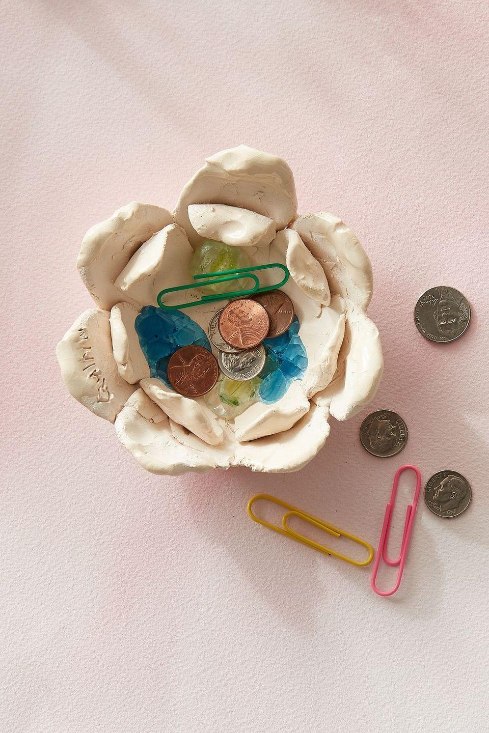 """<p> Kids will have so much fun crafting this catchall from <a href=""""https://www.amazon.com/Aestd-ST-Modeling-Non-Toxic-Non-Stick-Sculpting/dp/B08QZ69GJM/?tag=syn-yahoo-20&ascsubtag=%5Bartid%7C10070.g.2308%5Bsrc%7Cyahoo-us"""" rel=""""nofollow noopener"""" target=""""_blank"""" data-ylk=""""slk:oven baked clay"""" class=""""link rapid-noclick-resp"""">oven baked clay</a> — layer a smaller flower over a larger flower, then place a few plastic beads in the bottom and bake until hard. </p>"""