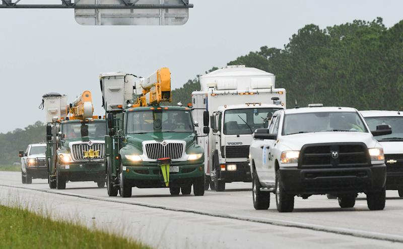 Utilities trucks head south on Interstate 95 to help restore power after Hurricane Dorian near Palm Bay, Fla.